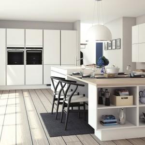 Meble z kolekcji Focus firmy HTH. Białe fronty otwierane bezuchwytowo nadają kuchni nowoczesnych charakter. Duża, funkcjonalna wyspa połączona została w wygodnym stołem pełniącym rolę jadalni. Jego drewniany blat, podobnie jak podłoga ociepla chłód bieli.