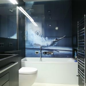W utrzymanej w czarnej kolorystyce łazience dużych rozmiarów fototapeta stanowi główny element dekoracyjny. Wybrany motyw pływaka podkreśla rekreacyjny charakter pomieszczenia, ale i jego ultranowoczesny wystrój. Projekt Monika i Adam Bronikowscy. Fot. Bartosz Jarosz.
