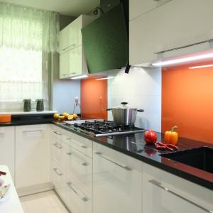 Ścianę nad blatem wykończono (tylko częściowo) lakierowanym szkłem w kolorze pomarańczowym, które ociepla wnętrze. Projekt: Zbigniew Bąba, Arkadiusz Jelito. Fot. Bartosz Jarosz.