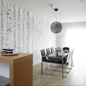 Dwie ogromne lampy wiszące nad stołem doskonale wpisują się w stylistykę wnętrza. Pasują zarówno do stołu, jak i do tapety na ścianie. Fot. Bartosz Jarosz.