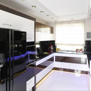 Kuchnia jest duża i funkcjonalna. Została wyposażona w szeroką gamę urządzeń AGD, a nawet telewizor. Fronty mebli kuchennych wykonano z białego MDF-u oraz hebanowego forniru, obu lakierowanych na wysoki połysk. Fot. Bartosz Jarosz.