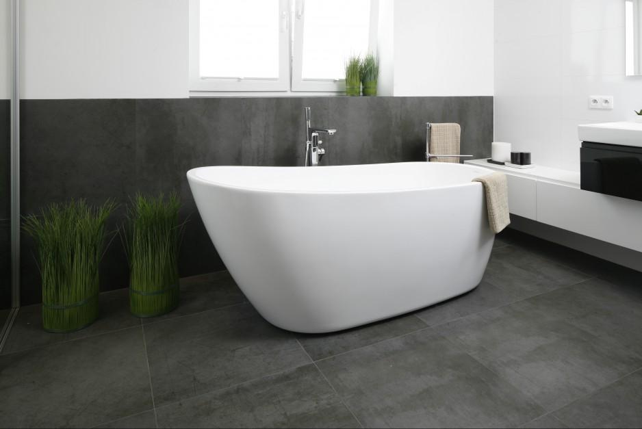 W utrzymanej w minimalistycznych szarościach łazience wolno stojąca wanna stanowi jej główny element dekoracyjny. Projekt Beata Kruszyńska. Fot. Bartosz Jarosz.