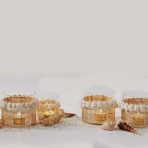 Świeczniki i lampiony dekorowane białymi muszelkami z oferty Riviera Maison to niepowtarzalna ozdoba, która doskonale sprawdzi się zarówno w domu, ogrodzie, jak i na tarasie. Fot. Riviera Maison.