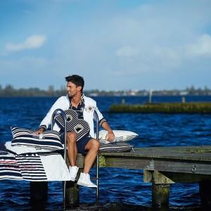 Dekoracyjne poduszki z oferty Riviera Maison utrzymane w charakterystycznych dla stylu marynistycznego barwach - białej, granatowej oraz czerwonej. Fot. Riviera Maison.