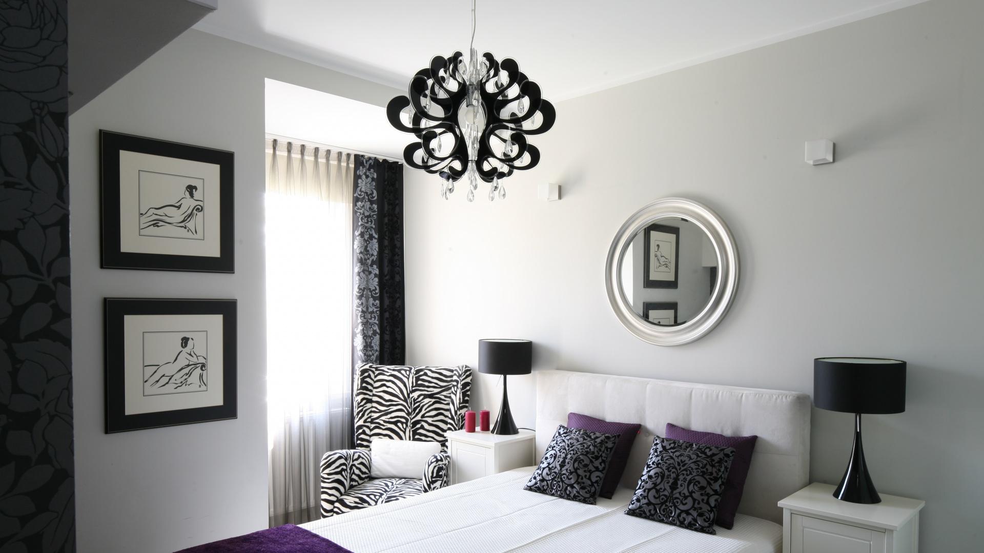 Lustro w ozdobnej ramie umieszczone nad łóżkiem dodaje wnętrzu elegancji i stanowi ciekawą dekorację, która stylistycznie nawiązuje do wystroju sypialni utrzymanej w stylu glamour. Proj.Małgorzata Galewska. Fot.Bartosz Jarosz.