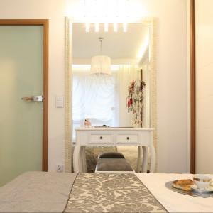 Lustro w bogato zdobionej ramie podkreśla charakter sypialni urządzonej w stylu glamour. Proj.Małgorzata Mazur. Fot.Bartosz Jarosz.