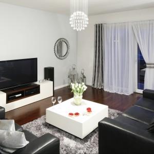 Skromna szafka stanowi znakomitą podstawę dla telewizora w nowoczesnym salonie. Projekt Magdalena Biały. Fot. Bartosz Jarosz.