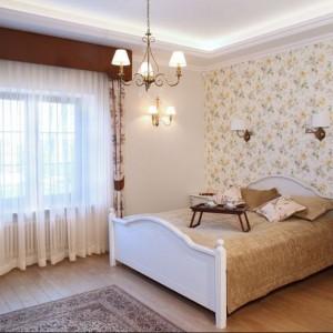 kwiecista tapeta umieszczona na jednej ścianie sypialni podkreśla klasyczny wystrój sypialni. Tapeta doskonale łączy się z motywem kwiatowym użytym na zasłonach.Proj.Maciej Bołtruczyk. Fot.Monika Filipiuk.