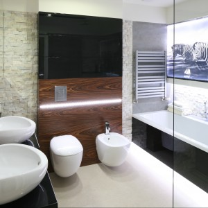 W bardzo reprezentacyjnej łazience funkcjonalność idzie w parze z estetyką. Stąd dwie umywalki o bardzo oryginalnych, organicznych kształtach umieszczono na czarnym, eleganckim blacie. Projekt Małgorzata Mazur. Fot. Bartosz Jarosz.