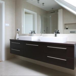W łazience na poddaszu strefa umywalkowa zaprojektowana została tak, by skosy nie przeszkadzały w codziennej toalecie. Organizuje ja duża podwieszana szafka, na której blatach zamontowano prostokątne umywalki. Projekt Karolina i Artur Urban. Fot. Bartosz Jarosz.