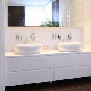 W białej, eleganckiej łazience strefa umywalkowa została zaprojektowana naprzeciwko wanny. Mimo wyraźnego rozgraniczenia na dwie oddzielne miejsca do toalety, tworzy ona jedna spójna stylistycznie całość. Projekt Katarzyna Mikulska-Sękalska. Fot. Bartosz Jarosz.