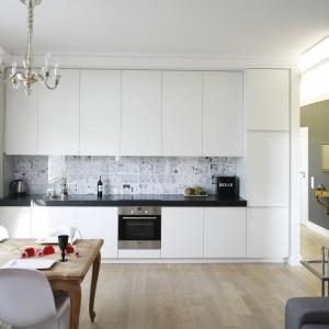 Kuchnia – zamknięta na jednej ścianie białej zabudowy – jest ergonomiczna i funkcjonalna. Szafki zagospodarowane są od podłogi do sufitu, dzięki czemu można w nich ukryć wszystkie akcesoria. Projekt: Monika Gorlikowska. Fot. Bartosz Jarosz.
