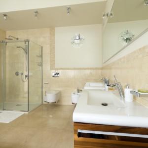 Zarówno ściany, jak i podłoga w tej dużej łazience wykończone są płytkami gresowymi w takiej samej, beżowej kolorystyce. Ciepła, jasna barwa rozjaśnia pomieszczenie i dodaje mu przestronności. Projekt Tomasz Tubisz. Fot. Przemysław Andruk.
