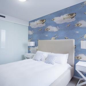 Białe meble doskonale prezentują się na tle niebieskiej ściany z białymi obłokami. Samoloty lecące w różnych kierunkach dynamizują tapetę.Fot.Dekornik.