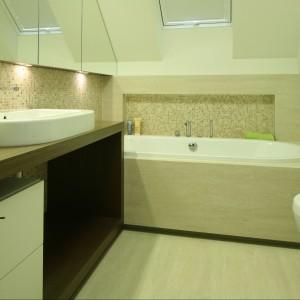 Łazienkę spowija kremowa biel. Dodaje ona pomieszczeniu przestrzeni oraz subtelnej elegancji,wprowadza wrażenie uporządkowania. Elementem ocieplającym łazienkę, o klasycznym, nieprzemijającym charakterze, jest również drewno. Projekt Ministerstwo Spraw we Wnętzach. Fot. Bartosz Jarosz.