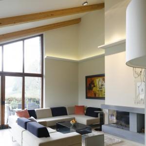Dzięki konstrukcji bryły część dzienna domu jest przestrzenna i doskonale doświetlona. Wzdłuż wszystkich ścian ciągnie się podświetlany ledami gzyms. Dodatkowym źródłem światła są także umieszczone nad kominkiem nowoczesne lampy. Projekt Małgorzata Borzyszkowska. Fot. Bartosz Jarosz.