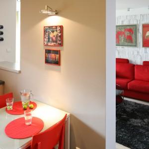 Niewielki stolik śniadaniowy świetnie sprawdza się jako kącik jadalniany. Podobnie jak krzesła został wybrany z oferty IKEA. Dodano im nieco indywidualnego charakteru – stolik zyskał nowy, szklany blat, a krzesła – czerwony kolor. Projekt: Marta Kruk. Fot. Bartosz Jarosz. Stylizacja: Ewa Kozioł.