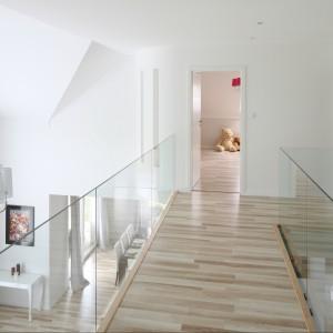 """Projekt domu, wykonany na indywidualne zamówienie, zakładał wszystkie rozwiązania funkcjonalne, których oczekiwali właściciele. Przede wszystkim przeszkloną antresolę z """"drewnianą kładką"""" na górze oraz salon wybijający się w górę na imponującą wysokość aż sześciu metrów! Te dwie przestrzenie, dodające wnętrzu oddechu, warunkowały rozkład wszystkich pozostałych pomieszczeń parteru, a w konsekwencji także poddasza. Są sercem domu i jego najbardziej reprezentacyjną częścią. Projekt Karolina i Artur Urban. Fot. Bartosz Jarosz."""
