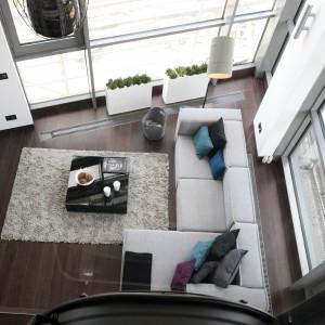 Prezentowany apartament to jednak nie tylko niesamowity, industrialny klimat, to także stuprocentowa funkcjonalność i wysoki standard wykończenia. Na dole mamy całkowicie otwartą część dzienną. Salon płynnie łączy się z kuchnią, jadalnią i wydzielonym – w obszernej strefie wejściowej – miejscem do pracy. Ogromne okna zastępują w tym miejscu elewację i doskonale doświetlają wszystkie pomieszczenia. Projekt Justyna Smolec. Fot. Bartosz Jarosz.