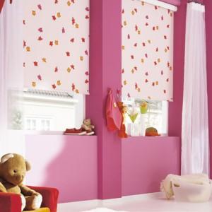 Jasne rolety w różowe i żółte wzory sprawdzą się w pokoju dziewczynki. Fot. Designer Curtains.