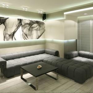 Utrzymany w minimalistycznych szarościach salon przyciąga i zaskakuje. A to za sprawą ciemnoszarej kanapy o pięknym, klasycznym pikowaniu, a przede wszystkim grafice tuż nad nią.  Projekt Dominik Respondek. Fot. Bartosz Jarosz.