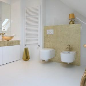 Nowoczesna, klarowna aranżacja łazienki bazuje na gładkich, białych powierzchniach i prostych formach wyposażenia. Jednak minimalistyczną konwencję przełamują bogate wykończenia i dodatki w złotym kolorze. Projekt Piotr Stanisz. Fot. Bartosz Jarosz.
