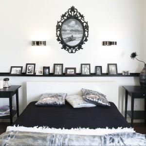 Czarne ramki ustawione na półce nad łóżkiem kontrastują z białą ścianą. Proj.Małgorzata Mazur. Fot.Bartosz Jarosz.