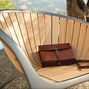 Krzesła z kolekcji Bella marki Gloster w aluminiowej ramie. Laminowane, zaokrąglone panele siedziska wykonano z drewna teakowego. Fot. Gloster.
