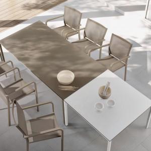 Stół i krzesła z kolekcji marki Manutti dostepne są w ciepłym kolorze piaskowym. Lekkość ich konstrukcji podkreśla materiał, z jakiego zostały wykonane - aluminium. Fot. Manutti.