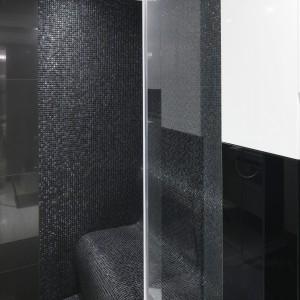 Kabina prysznicowa jest na tyle obszerna, że zmieściło się w niej wygodne siedzisko wykończone czarną, błyszczącą mozaiką. Jest nie tylko wygodnie, ale i bardzo efektownie. Projekt Agnieszka Hajdas-Obajtek, Fot. Bartosz Jarosz.