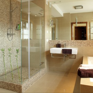 W utrzymanej w ciepłych beżach łazience panuje stylistyczny ład podporządkowany poszczególnym jej funkcjom. Stąd strefę prysznica wyznacza mozaika w naturalnych kolorach. Projekt Piotr Gierłatowski. Fot. Tomasz Markowski.