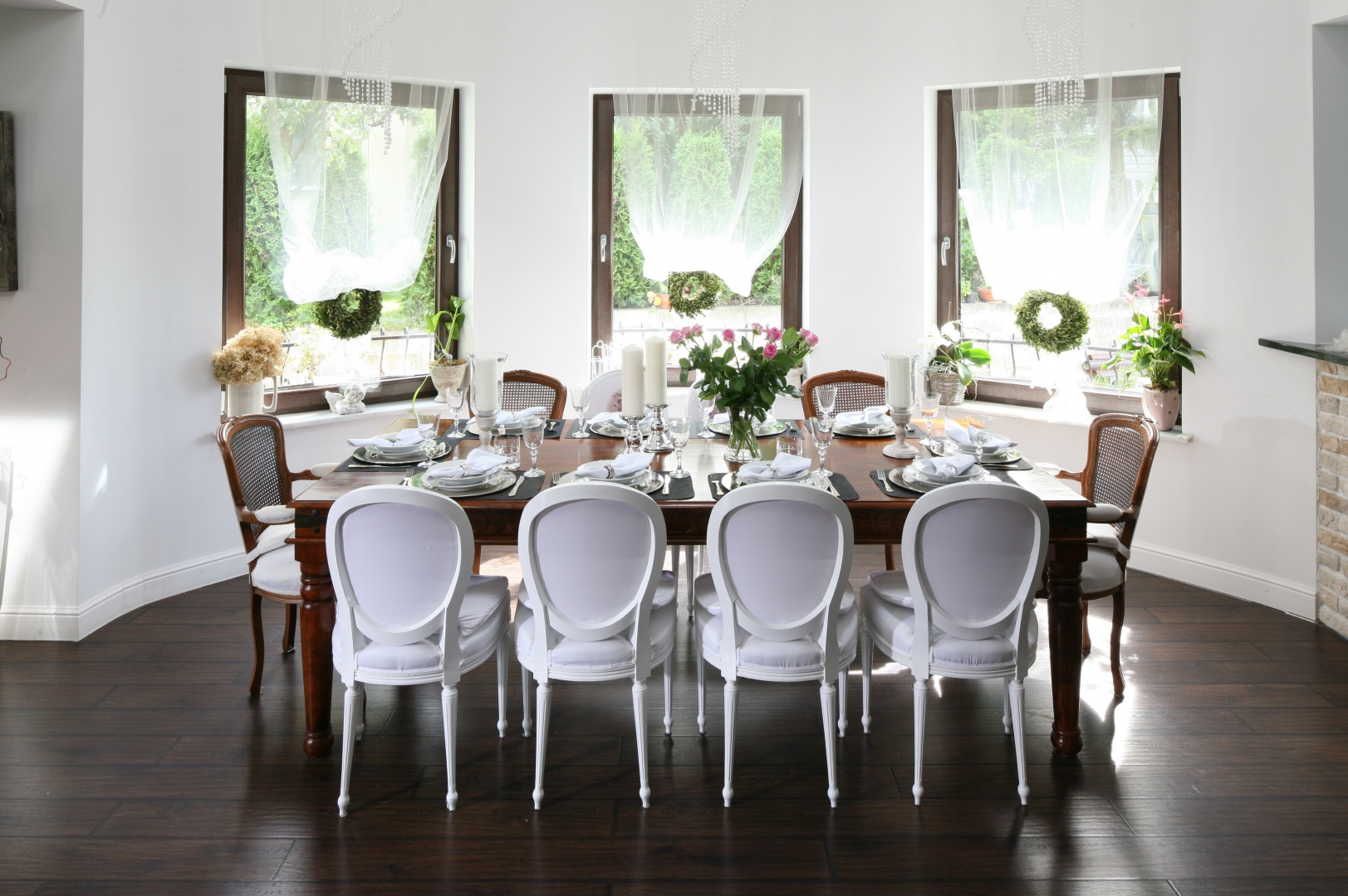 Drewno i biel prezentują się w tym wydaniu bardzo stylowo i z klasą. Duży stół pozwolił nie tylko na umieszczenie na nim pięknej zastawy, ale i udekorowanie go zarówno kwiatami, jak i eleganckimi świecznikami. Projekt wnętrza: Magdalena Konochowicz. Fot. Bartosz Jarosz.