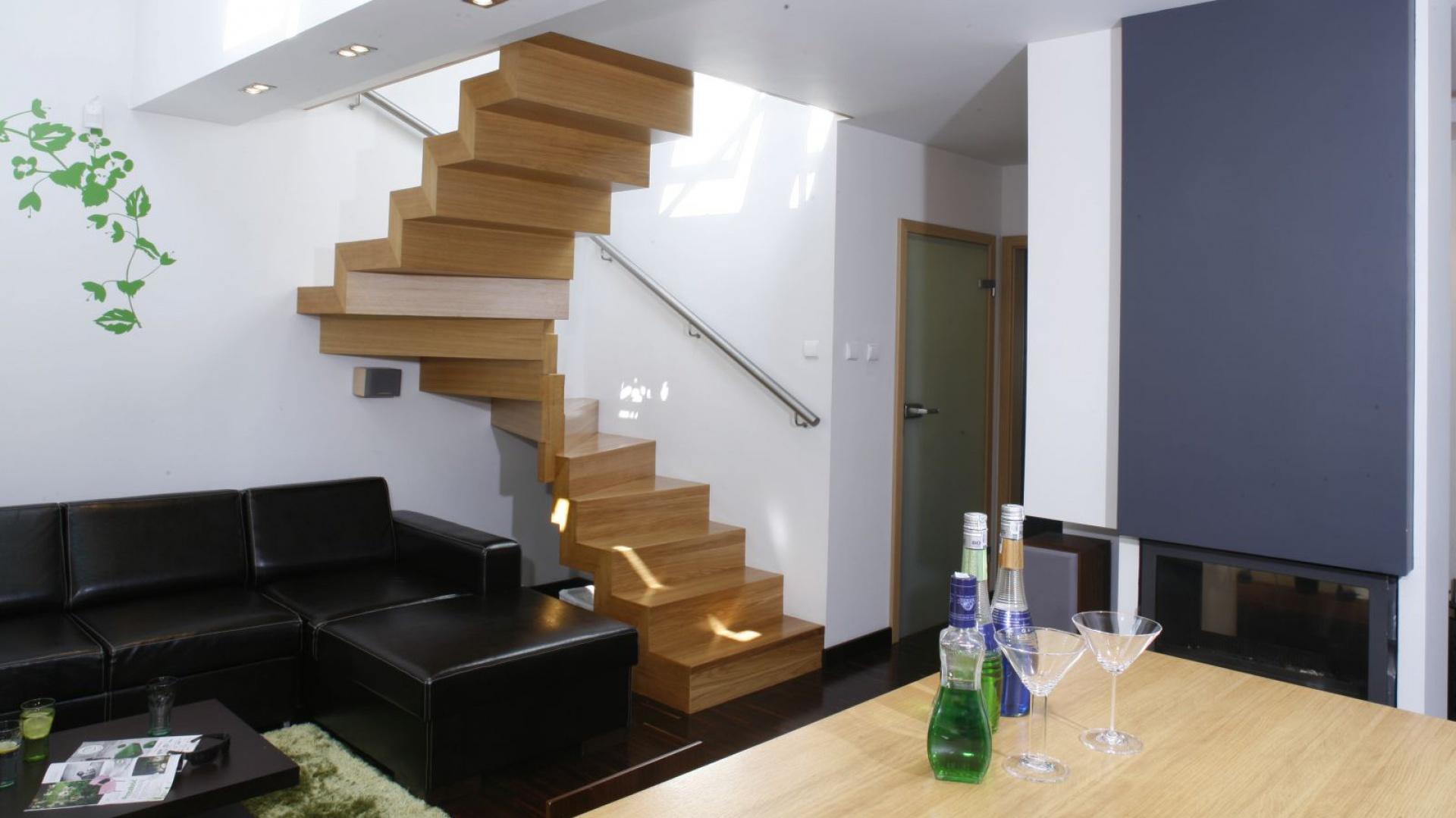 Nowoczesne, drewniane schody są efektownym detalem w aranżacji salonu. Fot. Archiwum Dobrze Mieszkaj.