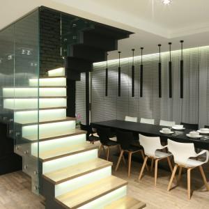 Masywne schody oddzielają w salonie strefę jadalnianą. Projekt: Dominik Respondek. Fot. Bartosz Jarosz.
