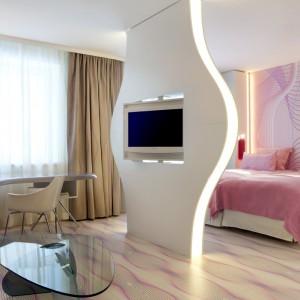Podświetlana ściana z ozdobną, futurystyczną tapetą na ścianie w odcieniu delikatnego różu. Proj. Karim Rashid.
