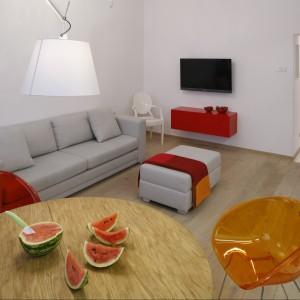 Chłodna biel ścian połączona z gorącą czerwienią i równie ciepłym oranżem dodatków pozwoliła stworzyć przytulny, lecz nie ciasny salonik. Strefę wypoczynkową tworzy tu jasnoszary zestaw mebli tapicerowanych marki Comforty. Projekt Agnieszka Żyła Fot. Bartosz Jarosz.