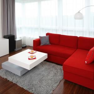 W salonie, zgodnie z początkowym założeniem projektowym, króluje czerwona sofa. Właściciel koniecznie chciał mieć ją w swoim mieszkaniu. Doskonale pasuje do niej oryginalny stolik kawowy składający się z dwóch połączonych ze sobą prostopadłościanów. Projekt Iza Szewc. Fot. Bartosz Jarosz.
