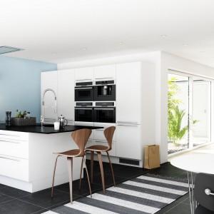 Meble z kolekcji Paris Hvid firmy Nettoline. Białe fronty o satynowej powierzchni w zestawieniu z czarnym blatem nadają całości nowoczesny, ale i elegancki charakter. Szerokie uchwyty ze stali nierdzewnej. Podwójnie szeroki blat oferuje mnóstwo miejsca na wszelkie kuchenne. Okap wbudowany jest w sufit.