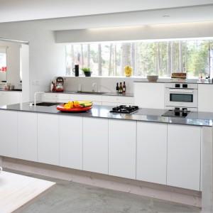 Meble z kolekcji Soled firmy Ballingslōv. Gładkie, białe fronty doskonale pasują do szarej kolorystki zastosowanej w kuchni, w której centralne miejsce zajmuje duża wyspa. Meble oferują sporą powierzchnię przechowywania oraz wygodne blaty robocze.