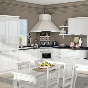 Meble z kolekcji Elin firmy Creo. Białe fronty szafek zostały ozdobione subtelnym, bardzo eleganckim frezem. Całość dopełnia stylowa zabudowa okapu oraz czteroosobowy stół.