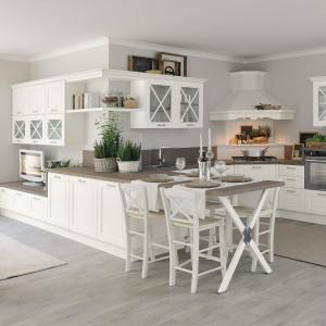 Meble z kolekcji Agnese firmy Lube Cucine. Białe fronty szafek z tradycyjnym frezowaniem ocieplają drewniane blaty. Czteroosobowy stół, na wzór półwyspu kuchennego, został w pełni zintegrowany z zabudową.