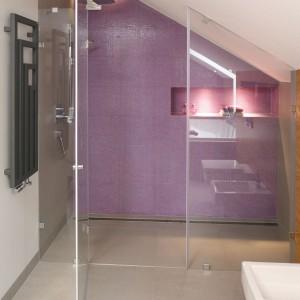 Mozaika w intensywnym, fioletowym kolorze zdobi ścianę tuż za prysznicem. Dodatkowo ożywia utrzymane w szaro-białej tonacji, bardzo stonowane wnętrze. Doskonale współgra również z ciepłym w odbiorze fornirem dębowym. Projekt Małgorzata Galewska. Fot. Bartosz Jarosz.