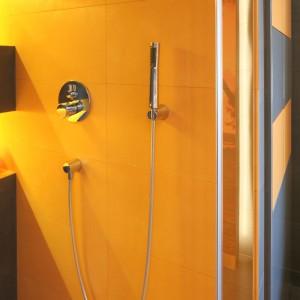 Pobudzająca do życia pomarańcza zdominowała strefę prysznica. W łazience, która stanowi wesołą enklawę młodych ludzi, zapewnia ona ekstremalną dawkę energii na każdy dzień. Projekt Monika i Adam Bronikowscy. Fot. Bartosz Jarosz.