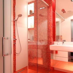 Łazienkę z dużą kabiną prysznicową zdobi kolor czerwony. Niezwykle efektowna mozaika, którą wyłożono ścianę za prysznicem, stanowi jej główny, choć nie jedyny element dekoracyjny. Projekt Małgorzata Szajbel-Żukowska, Maria Żychiewicz. Fot. Bartosz Jarosz.