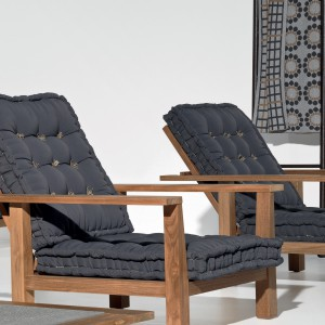 Duże, wygodne fotele z kolekcji InOut marki Gervasoni osadzono na niskich nóżkach, dzięki czemu doskonale mogą pełnić funkcję leżaka. wykonana z drewna teakowego rama idealnie współgra z czarnymi, pikowanymi poduchami. Fot. Gervasoni.