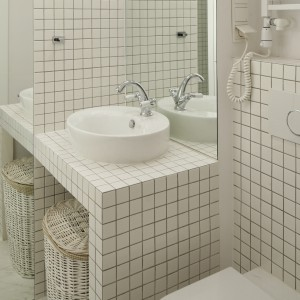 """Wszechobecna biel połączona z gra luster sprawia, iż mała łazienka nabiera """"oddechu"""". Ten zabieg świetnie tworzy iluzję powiększonej przestrzeni. Projekt Agnieszka Żyła. Fot. Bartosz Jarosz."""