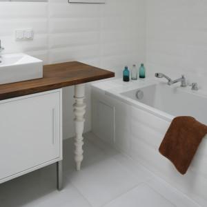 Łazienkę zaprojektowano tak, aby stworzyła inspirujący kontrast starego z nowym. Minimalistyczne umywalki osadzono na drewnianym blacie wspartym na wiekowych, dekoracyjnie frezowanych nogach.  Projekt Konrad Grodziński. Fot. Bartosz Jarosz.