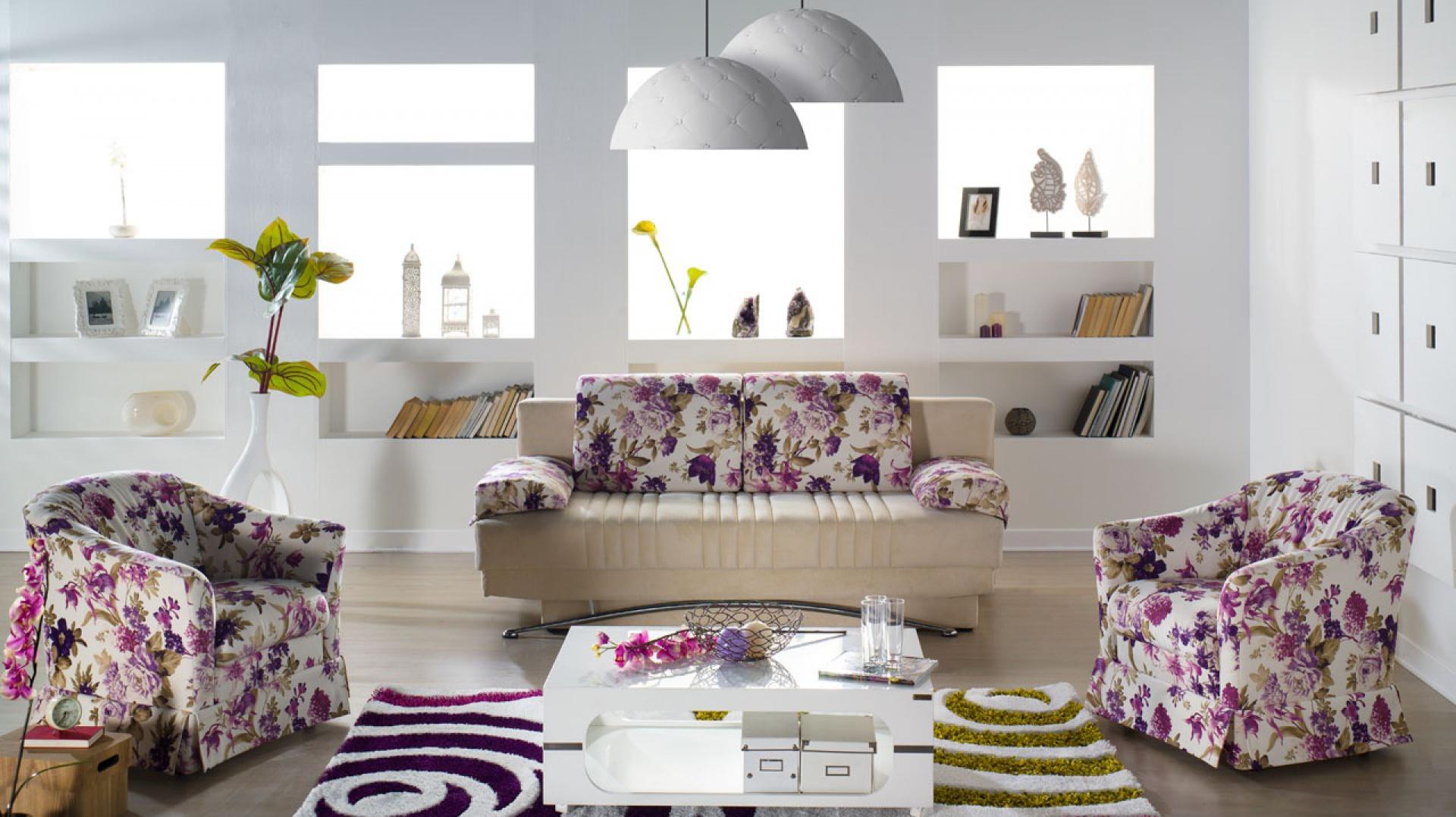 Bukiety fioletowych kwiatów na fotelach oraz kanapie nadają jasnemu wnętrzu romantyczny charakter. Fot. Istikbal.