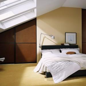 Zabudowa umieszczona na całej ścianie to praktyczne wykorzystanie nieustawnej przestrzeni pod skosami. Fot. Raumplus.