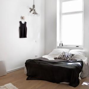 Ciemna narzuta oraz lustro efektownie ozdabiające ścianę ożywiają spokojne wnętrze. Fot. Fantastic Frank.
